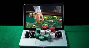 hand reaching through laptop for casino chips online casino gambling top casino sites